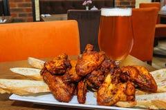Gebratene Hühnerflügel und Glas Bier stockbild