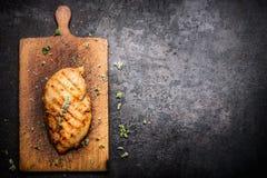 Gebratene Hühnerleiste auf gealtertem hölzernem Schneidebrett und dunklem Weinlesehintergrund, Grenze Stockfotos