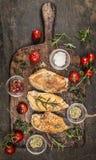 Gebratene Hühnerbrust mit gebratenen Kräutern und Tomaten auf rustikalem Schneidebrett, Draufsicht Stockbilder