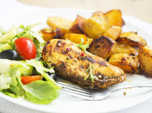 Gebratene Hühnerbrust mit Süßkartoffeln und Salat schmücken Stockbilder
