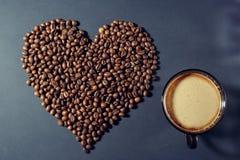 Gebratene Körner in Form eines Herzens und einer Schale aromatischen Kaffees auf einer Tabelle stockfotos