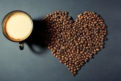 Gebratene Körner in Form eines Herzens und einer Schale aromatischen Kaffees auf einer Tabelle lizenzfreies stockbild