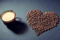 Gebratene Körner in Form eines Herzens und einer Schale aromatischen Kaffees auf einer Tabelle lizenzfreies stockfoto