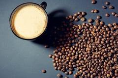 Gebratene Körner und eine Schale aromatischer Kaffee auf einer Tabelle in einer dunklen Art lizenzfreies stockfoto