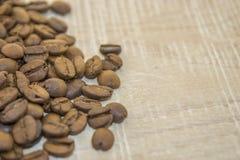 Gebratene Kaffeebohnen auf einem Holzfuß Stockbild