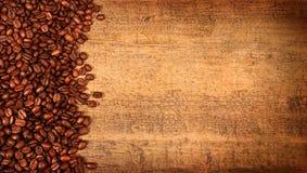 Gebratene Kaffeebohnen auf rustikalem Holz Lizenzfreie Stockbilder
