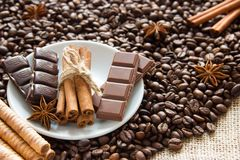 Gebratene Kaffeebohnen mit einem Bündel Zimtstangen mit Milch und schwarze Schokolade und Kekse auf dem Rausschmiß Lizenzfreies Stockbild