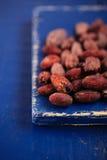 Gebratene Kakaoschokoladenbohnen auf dunkelblauem Holz stockbilder