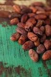 Gebratene Kakaoschokoladenbohnen auf hölzernem Hintergrund Stockfotografie