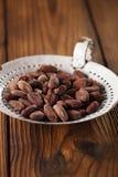 Gebratene Kakaoschokoladenbohnen im alten Emailsieb, strukturiert flehen an Lizenzfreie Stockfotografie