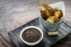 Gebratene Kartoffelkeile mit Soßensoße halten Snack-Food ab Lizenzfreies Stockbild