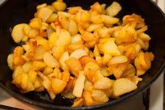 Gebratene Kartoffeln auf schwarzer Bratpfanne stockbilder