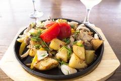 Gebratene Kartoffeln mit Fleisch und Tomaten in einer Roheisenbratpfanne stockfoto