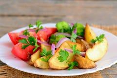 Gebratene Kartoffeln mit Gemüse Gebratene Kartoffelkeile, gekochter Brokkoli, neue Tomatenscheiben, rote Zwiebel, grüne Petersili stockfoto