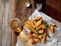 Gebratene Kartoffeln mit Kräutern auf einem Weißbuch, ein Glas Bier auf altem hölzernem Hintergrund, rustikale Art Stockbilder