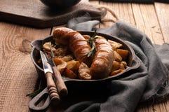 gebratene Kartoffeln und Würste in der Wanne mit Gabel, Messer, grauer Serviette und hackendem Brett stockfoto