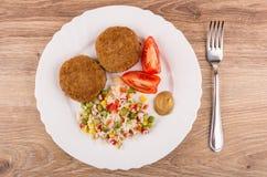 Gebratene Koteletts mit Gemüsemischung, Tomaten und Senf in der Platte Stockfotos