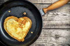 Gebratene Pfannkuchen - Herz auf einer Roheisenbratpfanne Lizenzfreie Stockfotos
