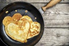 Gebratene Pfannkuchen - Herz auf einer Roheisenbratpfanne Lizenzfreies Stockbild