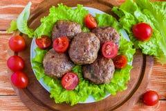 Gebratene Rindfleischkoteletts, grüner Salat und kleine Tomaten auf weißer Platte lizenzfreie stockfotografie