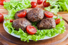 Gebratene Rindfleischkoteletts, grüner Salat und kleine Tomaten auf weißer Platte stockfotos