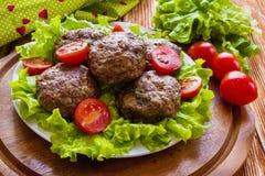 Gebratene Rindfleischkoteletts, grüner Salat und kleine Tomaten auf weißer Platte lizenzfreie stockfotos