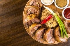 Gebratene Schweinefleisch-Roulade mit gekochtem Kohl und Soßen auf hölzernem Behälter Herauf Ansicht stockbild