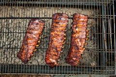 Gebratene Schweinefleischrippen mit Barbecue-Soße auf Grill im Freien Stockfotos