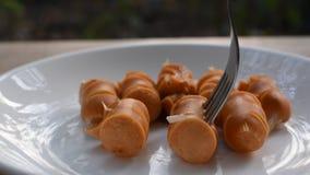 Gebratene Schweinswurstscheibe auf Teller und Erstechen durch die silberne Gabel, die Ketschup zurechtmacht, um zu essen stock footage