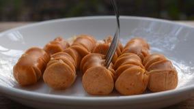 Gebratene Schweinswurstscheibe auf Teller und Erstechen durch silberne Gabel, um zu essen stock video