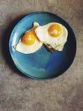 Gebratene Sonnenseite herauf Eier schoss Spitze unten auf blauer Platte Stockfotos