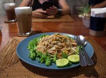 Gebratene thailändische Art der Nudel auf einer blauen Platte auf einer braunen Tabelle mit i lizenzfreies stockbild