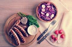 Gebratene Würste auf der Soße des Grills mit Sahne und einem Salat von radi Stockfoto