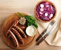Gebratene Würste auf der Soße des Grills mit Sahne und einem Salat von radi Lizenzfreie Stockfotos