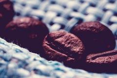 Gebratene, wohlriechende Kaffeebohnen Makro auf blauem Hintergrund Stockbilder