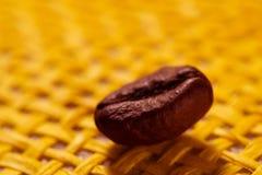 Gebratene, wohlriechende Kaffeebohnen Makro auf gelbem Hintergrund Lizenzfreie Stockfotografie