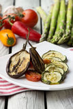 Gebratene Zucchini, Aubergine und grüner Pfeffer mit Tomatensauce Gebratenes Gemüse auf dem weißen rustikalen Hintergrund Stockfotos