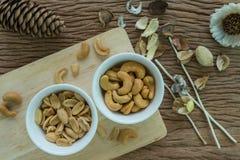 Gebratener Acajounuss- und Erdnussaperitif in der weißen Schüssel auf woode Lizenzfreies Stockbild