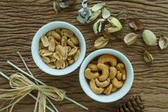 Gebratener Acajounuss- und Erdnussaperitif in der weißen Schüssel auf woode Lizenzfreie Stockfotos