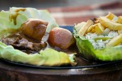 Gebratener Anstieg und Kartoffeln mit Gemüse und Fischen lizenzfreie stockbilder