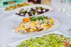 Gebratener Fischsalat mit verschiedenem Gemüse und einer Soße auf einem Weiß stockbild