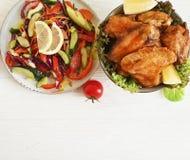 Gebratener Flügel gebratener Salat geschmackvoll auf einem köstlichen Pfeffer des hölzernen Hintergrundes zugebereitet lizenzfreies stockbild