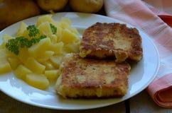 Gebratener Käse mit selbstgezogenen abgezogenen Kartoffeln auf hölzernem Hintergrund Stockfotos