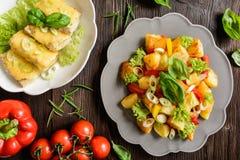 Gebratener Kartoffelsalat mit Kopfsalat, Pfeffer, Zwiebel und gebackener Fisch-FI Lizenzfreie Stockbilder