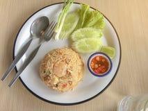 Gebratener Reis mit Garnele auf Thai verziert den Teller mit Frühlingszwiebel, Gurke, Kopfsalat, Paprikas und Zitrone stockfotografie