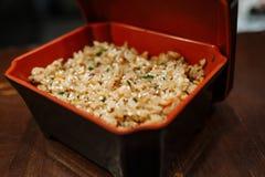 Gebratener Reis mit Gem?se in einem schwarzen rechteckigen Kasten mit rotem Darm auf einem Holztischhintergrund stockbilder