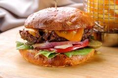 Gebratener Rindfleischhamburger mit Käse und Gemüsenahaufnahme Lizenzfreie Stockbilder