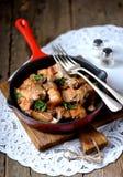 Gebratener Schweinebauch in einer Gusseisenbratpfanne mit Zwiebel, Knoblauch und Sojasoße Lizenzfreies Stockfoto