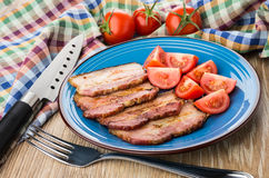 Gebratener Speck mit Tomaten in der Platte, Messer auf Serviette, Gabel Stockfotos