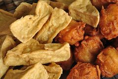 Gebratener Tofu und Süßkartoffel mischten im Mehl und in etwas indischem Sesam, die gebraten wurden Stockfotos
